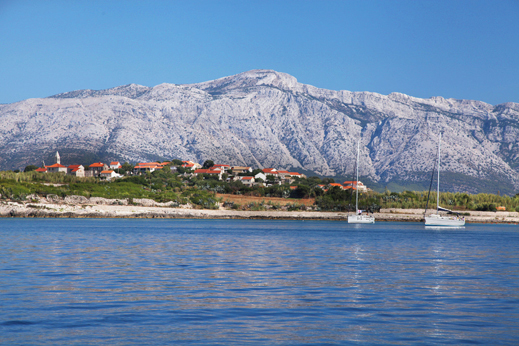 Sailing along Korcula island with Velebit mountain range in the background.