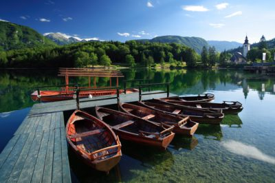 Boat rowing on crystal clear Bohinj Lake