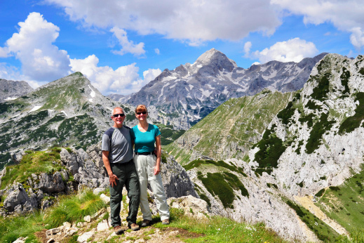 Happy hikers with amazing views in the heart of Julian Alps. Hut to Hut hiking Slovenia.