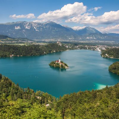 Bled Lake with islet and castle perched on a cliff. Karavanke mountain range in the background.